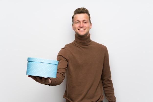 Uomo biondo sopra la parete bianca isolata che tiene un regalo in mano