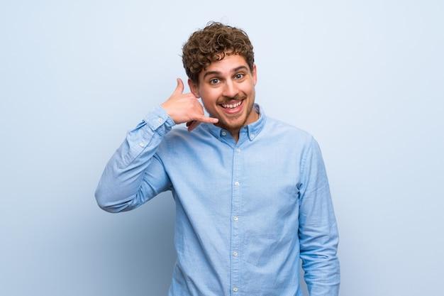 Uomo biondo sopra la parete blu che fa gesto del telefono. chiamami segno