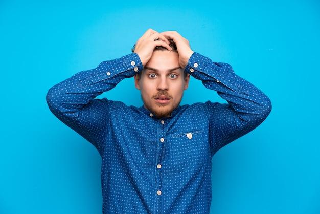 Uomo biondo sopra la parete blu isolata con espressione facciale sorpresa
