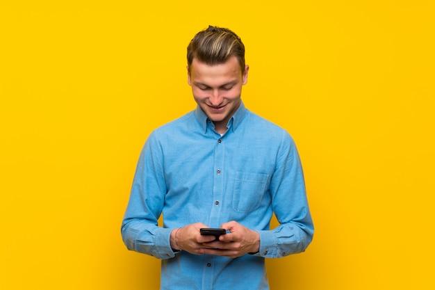 Uomo biondo sopra la parete gialla isolata che invia un messaggio con il cellulare