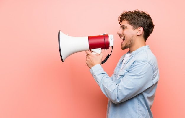 Uomo biondo sopra la parete rosa che grida tramite un megafono