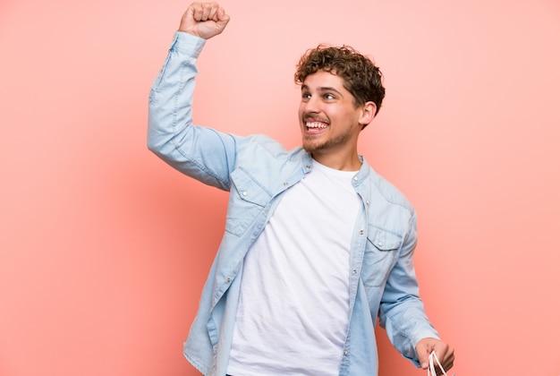 Uomo biondo sopra la parete rosa che tiene molti sacchetti della spesa nella posizione di vittoria