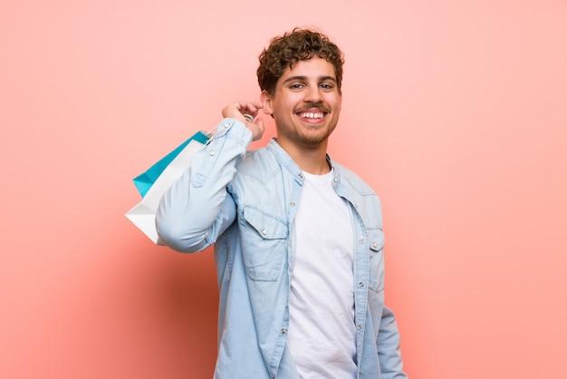 Uomo biondo sopra la parete rosa che tiene molti sacchetti della spesa