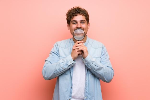 Uomo biondo sopra la parete rosa che tiene una lente d'ingrandimento