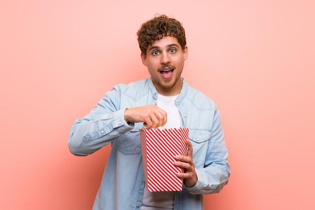 Uomo biondo sopra la parete rosa sorpreso e mangiando popcorn