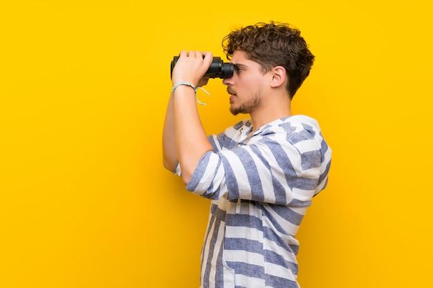Uomo biondo sul muro giallo e guardando in lontananza con il binocolo