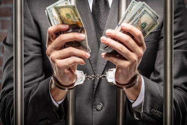 Uomo brasiliano che tiene le fatture di denaro con le manette