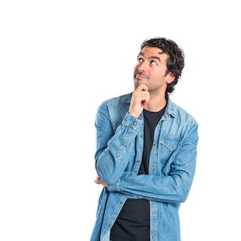 Uomo brunetta pensando su sfondo bianco isolato
