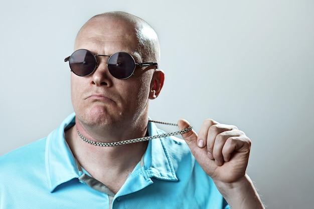 Uomo brutale calvo con occhiali rotondi e una camicia leggera tira una catenina d'argento