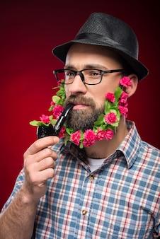Uomo brutale con fiori nella barba, cappello e pipa.