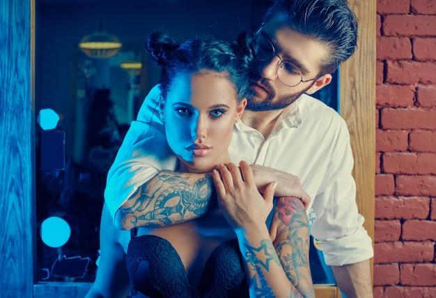Uomo brutale in abito elegante e ragazza sexy con tatuaggio