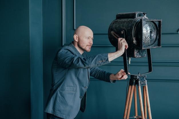 Uomo calvo adulto attraente con la barba in vestito che esamina il vecchio apparecchio di illuminazione, luce del video