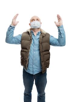 Uomo calvo adulto in una mascherina medica alzò le mani in preghiera. la crisi finanziaria e la quarantena durante la pandemia di coronavirus. misure precauzionali
