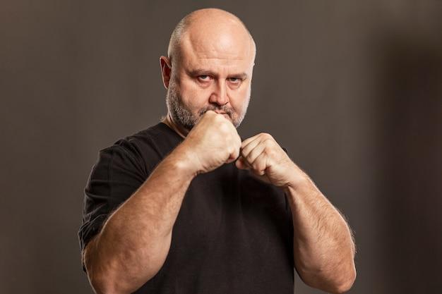 Uomo calvo adulto in una posizione di combattimento.