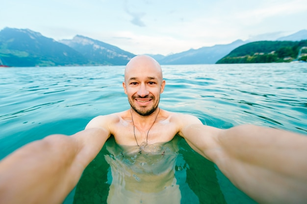 Uomo calvo felice che prende selfie nel lago di estate con le montagne
