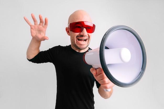 Uomo calvo in occhiali da sole rossi che grida in altoparlante