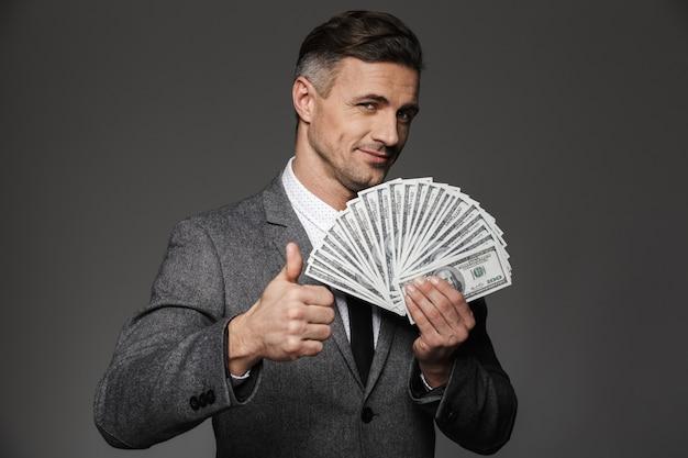 Uomo capo fortunato soddisfatto 30s in vestito di affari che tiene fan di valuta dollaro denaro contante e che mostra il pollice in su, isolato sopra il muro grigio