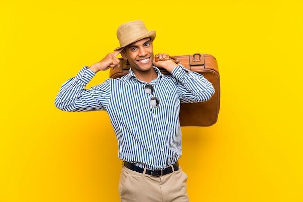 Uomo castana che tiene una cartella d'annata sopra la parete gialla isolata che intende realizzare la soluzione
