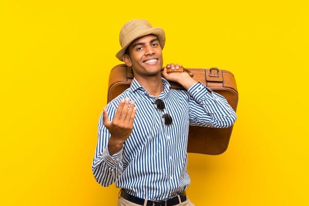 Uomo castana che tiene una cartella d'annata sopra la parete gialla isolata che invita a venire con la mano. felice che tu sia venuto