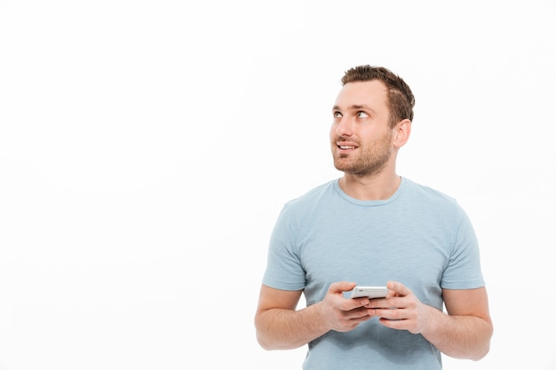 Uomo castana positivo che ha setola che sorride e che guarda da parte mentre usando lo spazio della copia dello smartphone