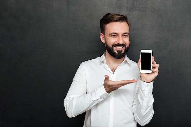 Uomo castana positivo che mostra smartphone sulla dimostrazione della macchina fotografica o sull'aggeggio di pubblicità sopra lo spazio della copia della grafite