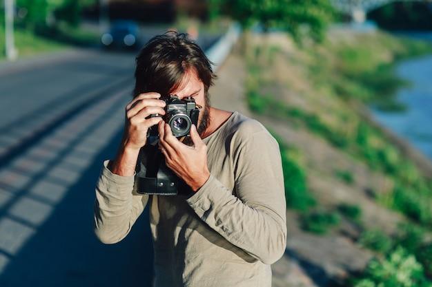 Uomo casuale dei pantaloni a vita bassa che fa foto facendo uso della retro macchina fotografica all'aperto nel parco