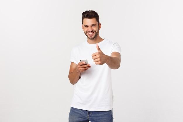 Uomo casuale felice con lo smartphone e pollice in su sopra grey