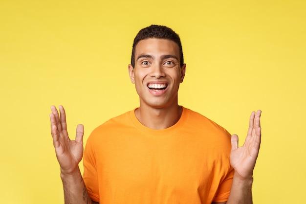 Uomo caucasico attraente ed eccitato in maglietta che mostra scatola o qualcosa di grande, allarga le mani vicino al petto per formare un grande oggetto