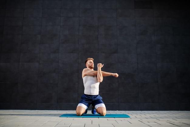 Uomo caucasico barbuto muscolare bello che si inginocchia sulla stuoia all'aperto e che allunga le sue braccia. sullo sfondo è il muro grigio.