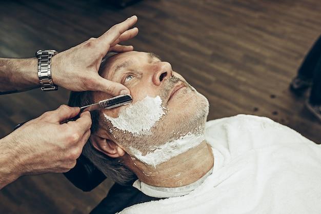 Uomo caucasico barbuto senior bello laterale di vista superiore laterale del primo piano che ottiene governare barba nel parrucchiere moderno. parrucchiere che serve il cliente, facendo un taglio di capelli con la barba usando il rasoio. concetto di negozio di barbiere.