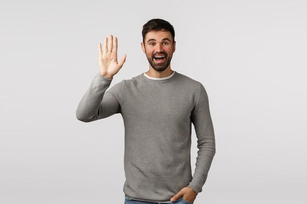 Uomo caucasico barbuto sorridente amichevole, allegro ed estroverso, saluto vicino che solleva braccio e che saluta ciao, ciao gesto, vede la persona come aspettando nel punto d'incontro