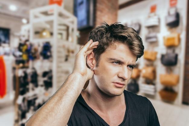 Uomo caucasico che ha problemi dell'udito che ascoltano qualcosa