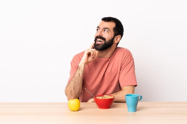 Uomo caucasico che mangia prima colazione in una tavola che pensa un'idea mentre guardando su
