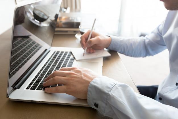 Uomo caucasico che per mezzo del computer portatile alla tabella
