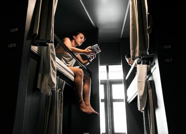 Uomo caucasico che si siede sul letto di cuccetta che legge il libro di guida di viaggio di bangkok tailandia