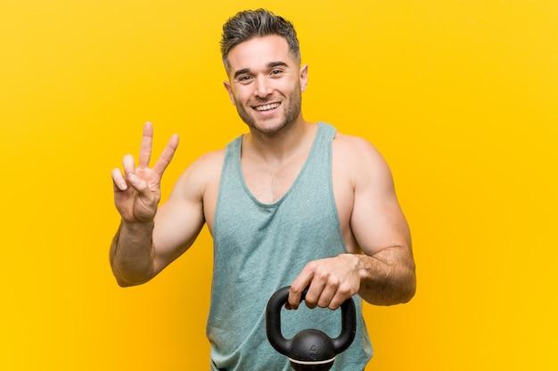 Uomo caucasico che tiene un bumbbell che mostra numero due con le dita.