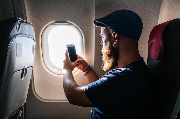 Uomo caucasico che utilizza telefono nell'aeroplano