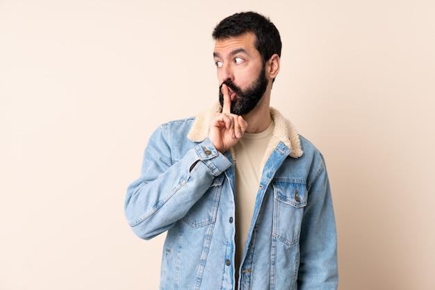 Uomo caucasico con barba sopra isolato mostrando un segno di silenzio gesto mettendo il dito in bocca