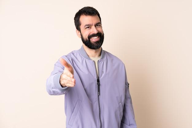 Uomo caucasico con la barba che indossa una giacca isolata agitando le mani per chiudere un buon affare