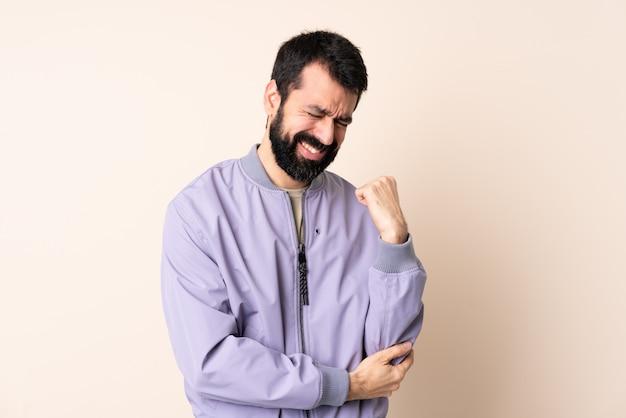 Uomo caucasico con la barba che indossa una giacca sopra isolata con dolore al gomito