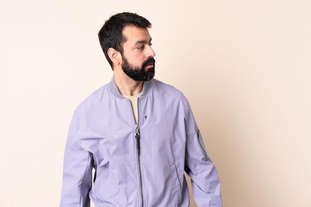 Uomo caucasico con la barba che indossa una giacca sopra isolato guardando al lato