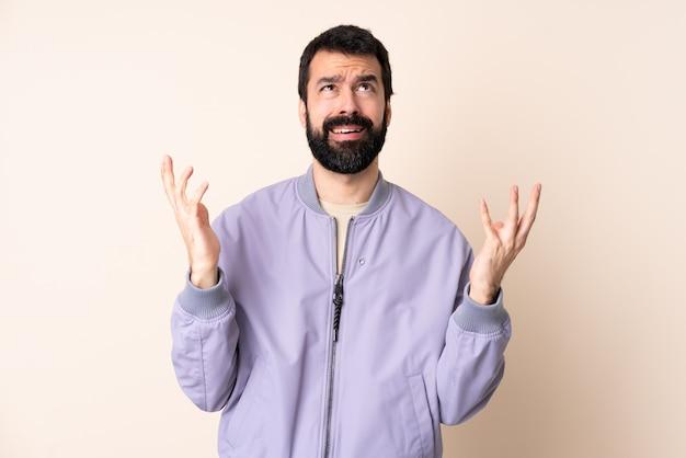 Uomo caucasico con la barba che indossa una giacca sopra isolato stressato sopraffatto