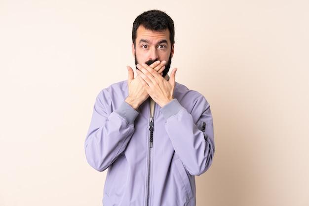 Uomo caucasico con la barba che indossa una giacca sopra la bocca di copertura isolata con le mani