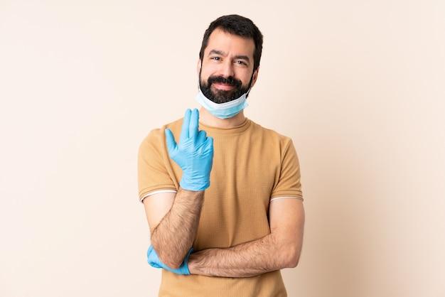 Uomo caucasico con la barba che protegge con una maschera e guanti sopra la parete isolata che invita a venire con la mano. felice che tu sia venuto