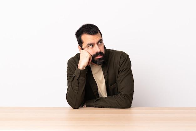 Uomo caucasico con la barba in un tavolo con espressione stanca e annoiata