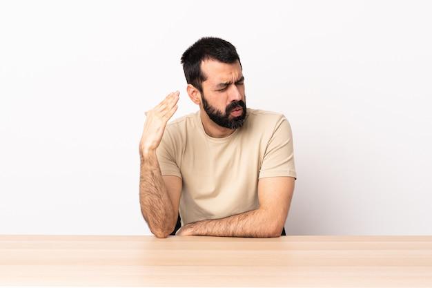 Uomo caucasico con la barba in un tavolo con espressione stanca e malata.