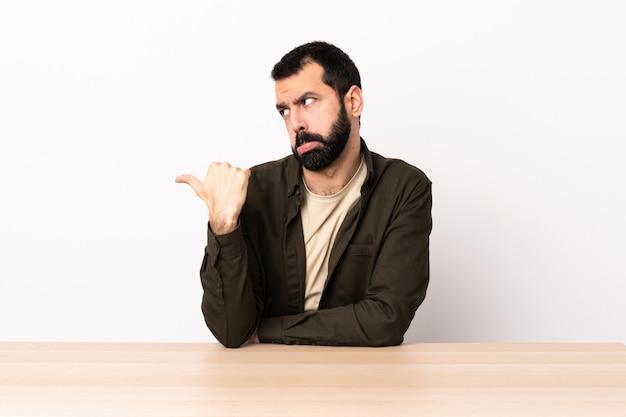 Uomo caucasico con la barba in un tavolo infelice e che punta verso il lato