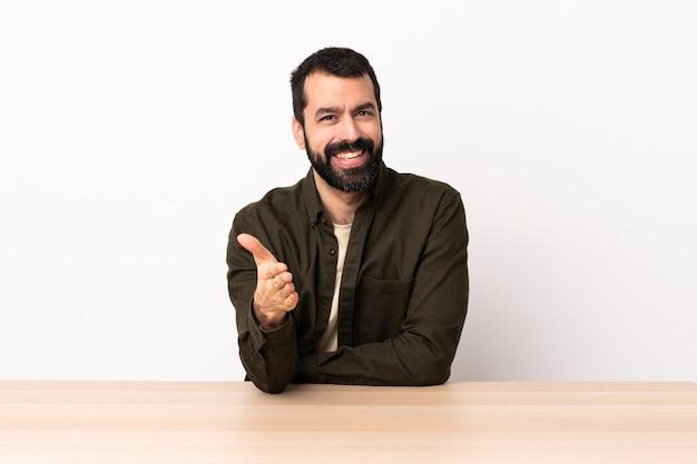 Uomo caucasico con la barba in un tavolo si stringono la mano per chiudere un buon affare