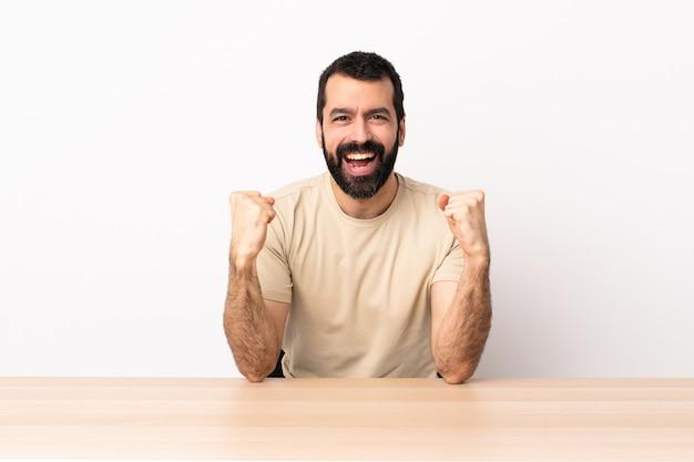 Uomo caucasico con la barba in una tabella che celebra una vittoria nella posizione del vincitore.