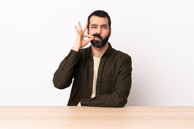 Uomo caucasico con la barba in una tabella che mostra un segno di silenzio gesto